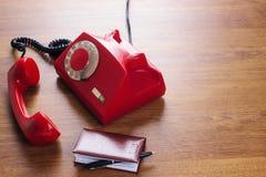 Винтажный вращая красный телефон диска и книга телефона стоковое фото rf