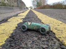 Винтажный гоночный автомобиль игрушки, принятый на реальную предпосылку дороги показывая двойные желтые линии идя в расстояние, р Стоковое фото RF