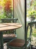 Винтажный деревянный стол и стул в стеклянной комнате около сада стоковое изображение rf