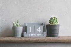 винтажный деревянный календарь на 14-ое февраля на деревянных влюбленности таблицы и va Стоковая Фотография