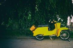 Винтажный желтый Vespa паркуя иконический итальянский конструированный самокат стоковые фотографии rf