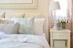 Винтажный интерьер спальни с подушками цветка и декоративной настольной лампой Стоковая Фотография
