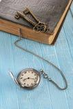 Винтажный карманный вахта, старая книга и латунный ключ Стоковое Изображение