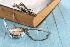 Винтажный карманный вахта, старая книга и латунный ключ Стоковое фото RF