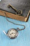 Винтажный карманный вахта, старая книга и латунный ключ Стоковая Фотография