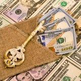 Винтажный ключ лежит на мешковине и американской валюте Символ  Стоковые Фотографии RF