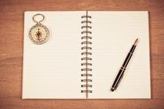 Винтажный компас на примечании и авторучке книги Стоковое Изображение