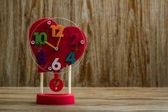 Винтажный красный будильник с формой сердца на деревянной предпосылке Стоковая Фотография