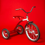 Винтажный красный трицикл на яркой красной предпосылке Стоковое Изображение RF