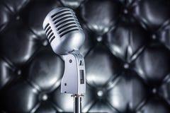 Винтажный микрофон на черной кожаной предпосылке Стоковые Фото
