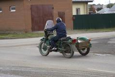 Винтажный мотоцикл с sidecar на проселочных дорогах около городка  стоковые изображения