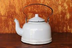 Винтажный покрытый эмалью чайник на старой деревянной таблице стоковые изображения rf