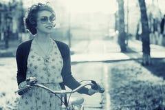 Винтажный портрет девушки с велосипедом Стоковые Фото