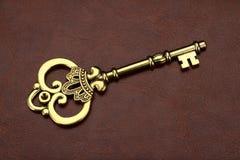 Винтажный/ретро золотой ключ на коричневой кожаной предпосылке Стоковая Фотография RF