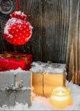 Винтажный состав рождества при подарочные коробки обернутые в бумаге, свече и снеге kraft Стоковая Фотография