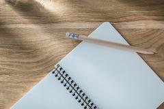 Винтажный спиральный карандаш тетради с прописями на взгляд сверху деревянной доски Стоковое Изображение