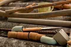 Винтажный старый нож и пластиковый шланг трубы воды на грязной рифленой крыше - Moldy конкретной текстуре стоковое фото