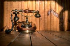 Винтажный телефон на деревянном столе с деревянной предпосылкой на солнце стоковое изображение rf