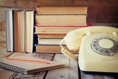 Винтажный телефон шкалы, книга телефона рядом с стогом старых книг над деревянным столом изображение фильтрованное годом сбора ви стоковое изображение
