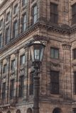 Винтажный уличный фонарь против королевского дворца на квадрате запруды в Амстердаме стоковое изображение
