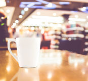 Винтажный фильтр: Белая кофейная чашка на деревянной таблице на bac кафа нерезкости Стоковые Изображения RF