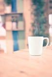 Винтажный фильтр: Белая кофейная чашка на деревянной таблице на bac кафа нерезкости Стоковая Фотография RF