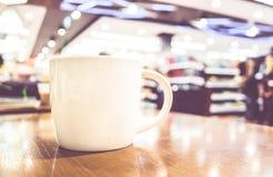 Винтажный фильтр, белая кофейная чашка на деревянной таблице с запачканным кафем Стоковое Фото