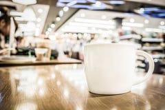 Винтажный фильтр, белая кофейная чашка на деревянной таблице с запачканным кафем Стоковая Фотография RF