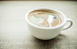 Винтажный фильтр: Закройте вверх по кофейной чашке эспрессо на деревянной таблице в ca Стоковые Фотографии RF