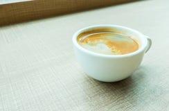 Винтажный фильтр: Закройте вверх по кофейной чашке эспрессо на деревянной таблице в ca Стоковые Изображения RF