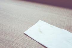 Винтажный фильтр: Салфетка с пятном кофе на деревянной таблице Стоковые Фотографии RF