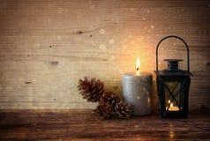 Винтажный фонарик с горящими свечами, конусами сосны на деревянном столе и предпосылкой светов яркого блеска Фильтрованное изобра Стоковое Фото
