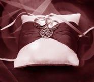 Винтажный фотоснимок обручальных колец на белой подушке с красной лентой Стоковые Изображения RF