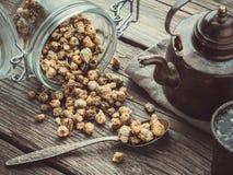 Винтажный чайник, стеклянный опарник сухих здоровых бутонов стоцвета, ложка и ретро чашка чая маргариток травяного на деревянном  стоковые изображения