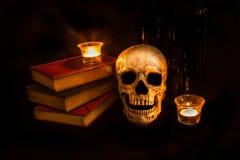 Винтажный череп и романы светом горящей свечи стоковое изображение rf