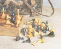 Винтажный шахмат и старая кожаная сумка на деревянной поверхности Стоковые Изображения