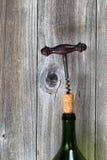 Винтажный штопор извлекая пробочку от бутылки вина с деревянным backg стоковое изображение