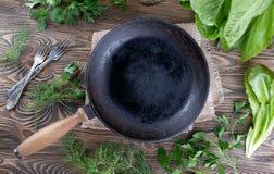 Винтажный skillet литого железа на деревенской деревянной предпосылке с травами Стоковое Изображение RF