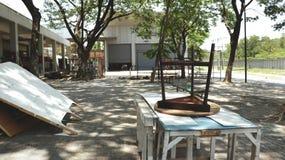 Винтажным вверх ногами табуретки Брайна трехногим положенное стулом на античных деревенских таблицах - под деревом в покинутом га Стоковая Фотография RF