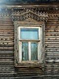 Винтажным окно высекаенное взглядом деревянного дома в старом русско стоковые изображения