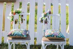 2 винтажных белых стуль, красочной подушка бархата и палисад загородки на предпосылке украшенной с цветками в стиле boho Мягкое e Стоковая Фотография RF