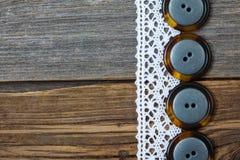 4 винтажных кнопки и античного шнурок на старых досках постарели плата Стоковое фото RF