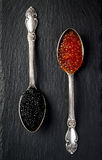 2 винтажных серебряных ложки с красными семгами и черной икрой стерляжины на черном шифере облицовывают предпосылку Взгляд сверху Стоковые Фото