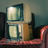 2 винтажных телевидения на красном кресле Стоковые Фото