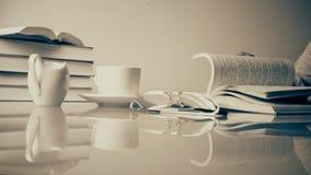 Винтаж кино старое стеклянный стол с книгами и чашкой чаю женщина читая книгу и выпивая чай monochrome сток-видео