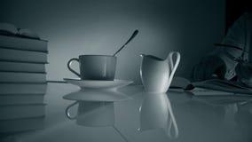Винтаж кино старое стеклянный стол с книгами и чашкой чаю женщина читая книгу и выпивая чай monochrome видеоматериал
