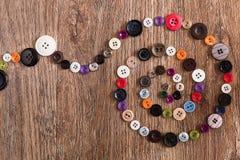 Винтовая линия красочный шить застегивает на деревянной предпосылке Стоковая Фотография