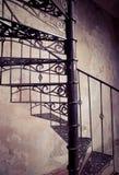 Винтовая лестница металла против старой предпосылки стены Стоковое Изображение