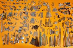 Винты, болты, гайки, крепежные детали на апельсине Стоковое Фото