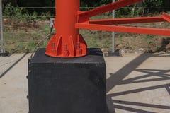Винты и гайки на основании красного электрического столба от металла Стоковые Фотографии RF